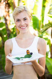 Happy blonde woman presenting plate with herbal medicine Stock Photos