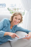 Happy blonde woman relaxing on her couch using her tablet Stock Image