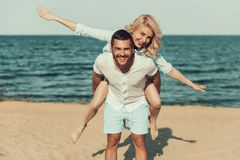 Happy blonde woman sits on mans back, near seaside. stock photos
