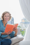 Happy blonde woman sitting on her couch holding a book Royalty Free Stock Photos