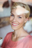 Happy blonde woman smiling at camera and holding a cup of coffee Royalty Free Stock Image