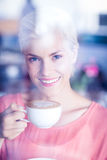 Happy blonde woman smiling at camera and holding a cup of coffee Stock Photography