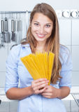 Happy blonde woman with spaghetti at kitchen Royalty Free Stock Photography