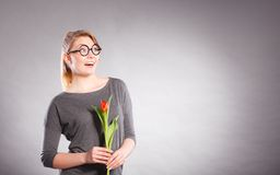 Happy blonde woman with spring flower. Happiness and satisfaction with life. Blonde woman wearing eyewear with single red green tulip. Happy joy girl feeling stock photography