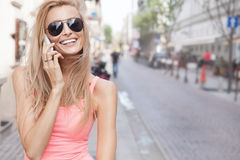 Happy blonde woman talking by mobile phone. Stock Image
