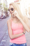 Happy blonde woman talking by mobile phone. Royalty Free Stock Photo