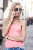 Happy blonde woman talking by mobile phone. Stock Photography