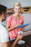 Happy blonde woman using tablet and looking her boyfriend Royalty Free Stock Photo