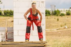 Woman in dungarees working on construction site royalty free stock image