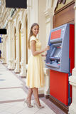 Happy blonde woman withdrawing money from credit card at ATM Stock Photo