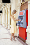 Happy blonde woman withdrawing money from credit card at ATM Royalty Free Stock Images