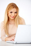 Happy blonde woman working on a laptop Royalty Free Stock Images