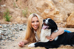 Happy blonde young woman hugging her dog on the beach Stock Photo