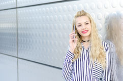 Happy blonde young woman outdoor using her mobile phone isolated Stock Image