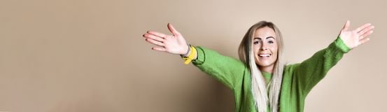 Happy blonde young woman shows welcome gesture, spreads hands as wants to cuddle best friend. Smiles broadly, wears green sweater. Come to me! BANNER stock photography