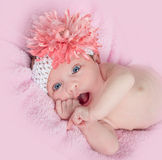 Happy blue eyed baby girl with a headband and flower royalty free stock photography