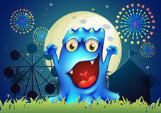 A happy blue monster in front of the amusement park Stock Images