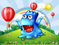 A happy blue monster at the hilltop with the floating balloons Royalty Free Stock Images