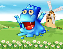 A happy blue monster at the hiltop with a windmill Royalty Free Stock Photos