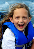 Happy on a boat. Girl happy on a boat with life vest royalty free stock images