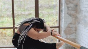 Concept of natural diverse beauty and sport. Happy body positive fat woman with dreadlocks doing stretching in the gym