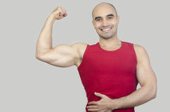 Happy bodybuilder showing his biceps. Stock Photo