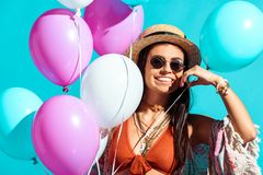 Happy bohemian girl standing with helium balloons. Isolated on turquoise stock photo