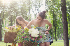 Happy boho chic girls gather wild flowers on bicycle ride. Happy boho girls gather wild flowers on bicycle ride. Beautiful female friends, youth and happiness royalty free stock image