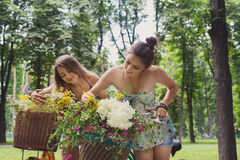 Happy boho chic girls gather wild flowers on bicycle ride. Boho girls gather wild flowers on bicycle ride. Beautiful female friends, youth and happiness, active stock photos