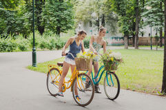 Happy boho chic girls gather wild flowers on bicycle ride. Happy boho girls gather wild flowers on bicycle ride. Beautiful female friends, youth and happiness royalty free stock photo