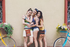 Happy boho chic girls pose with bicycles near house facade stock image