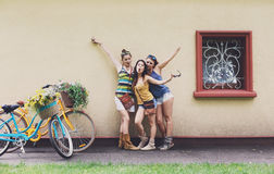 Happy boho chic girls pose with bicycles near house facade royalty free stock photography