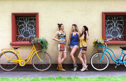 Happy boho chic girls pose with bicycles near house facade stock photography