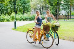 Happy boho chic girls ride together on bicycles in park royalty free stock image