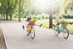 Happy boho chic girls ride together on bicycles in park stock images