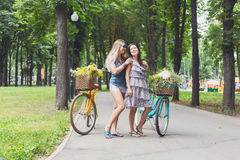 Happy boho chic girls ride together on bicycles in park Stock Photos
