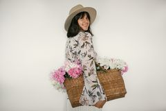 Happy boho girl smiling and holding pink and white peonies in rustic basket. Stylish hipster woman in hat and bohemian floral royalty free stock images