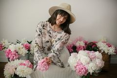 Happy boho girl smiling at pink and white peonies on rustic wooden floor. Stylish hipster woman in hat and bohemian floral dress stock photo