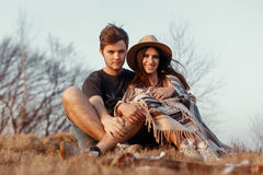 Happy boho hipster couple hugging and sitting at sunset in mount Stock Images