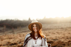 Happy boho woman hipster, smiling at sunset in mountains, wearing hat and poncho, true emotions, space for text stock photos