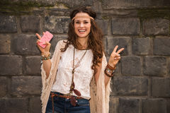Happy boho young woman near stone wall showing victory gesture Stock Images