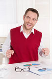 Happy bookkeeper with fists at desk at office. Stock Images