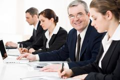 Happy boss. Confident businessman looking at camera among his employees at briefing stock photos