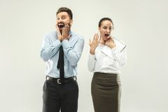 Happy boss. Man and his secretary standing at office. Or studio. Business man showing the phone to his colleague. Female and male caucasian models. Office Stock Image