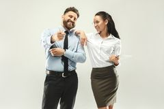 Happy boss. Man and his secretary standing at office. Or studio. Business man showing to his colleague something. Female and male caucasian models. Office Royalty Free Stock Image