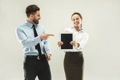 Happy boss. Man and his secretary standing at office. Or studio. Business men showing to his colleague something on laptop. Female and male caucasian models Stock Photography