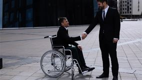 Happy Boss Shaking Hands With Cripple Colleague Outdoor stock video footage