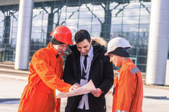 Happy boss snf team of  young engineers with construction projec. T. They wear overalls and safety helmets. Business modern background Stock Photography
