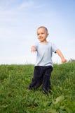 Happy boy. Happy running boy. Motion blur. Blue sky. Green grass Stock Image