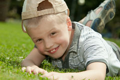 Happy boy. Portrait of a happy child lying on the grass and smiling Stock Image